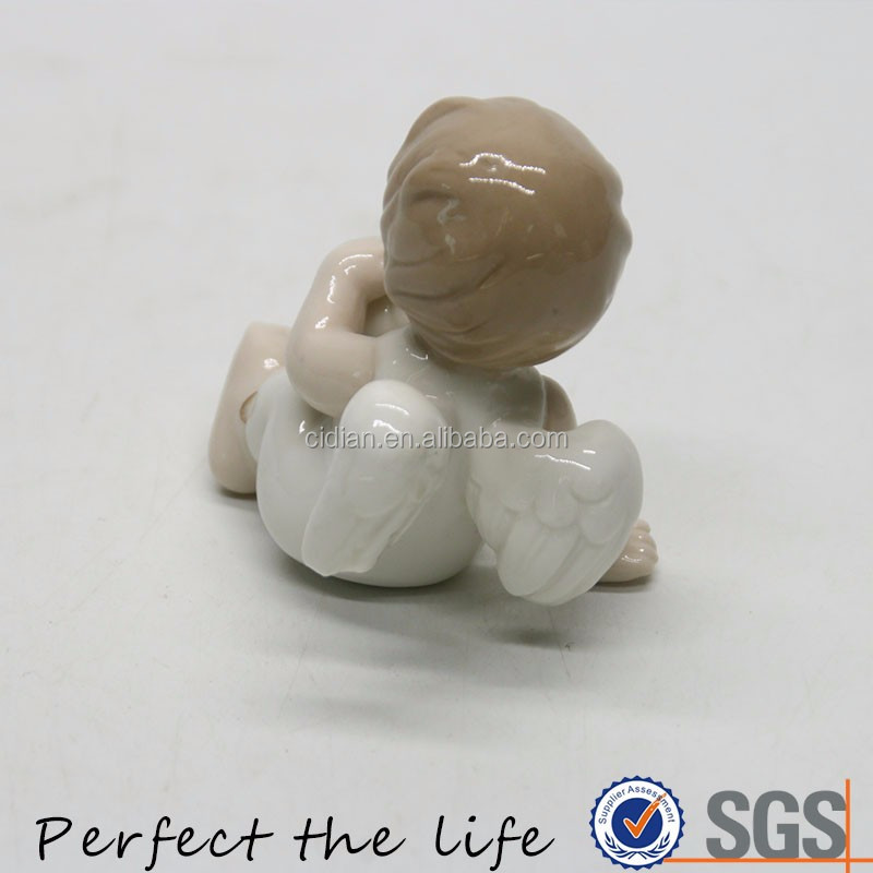 Lie down sitting ceramic cherub with a football in hands