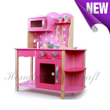 round pink wooden kitchen toy set with multiple kitchen ware set