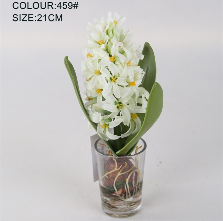 Artificial cream hyacinth flower with fake water in glass cup