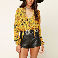 A woven top with an allover ornate print self-tie neck long cuff sleeves short t-shirt