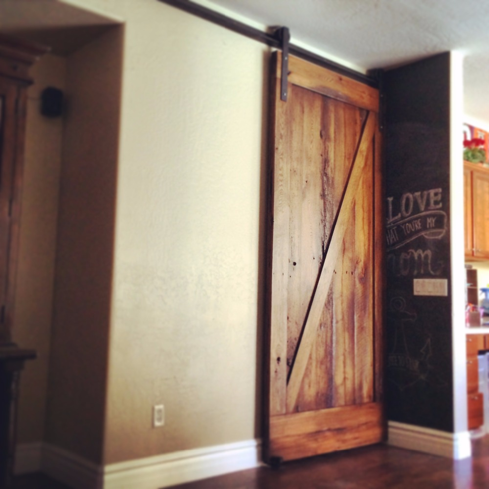 Rustic knotty alder stile & rail stained wood interior barn door with flat panels